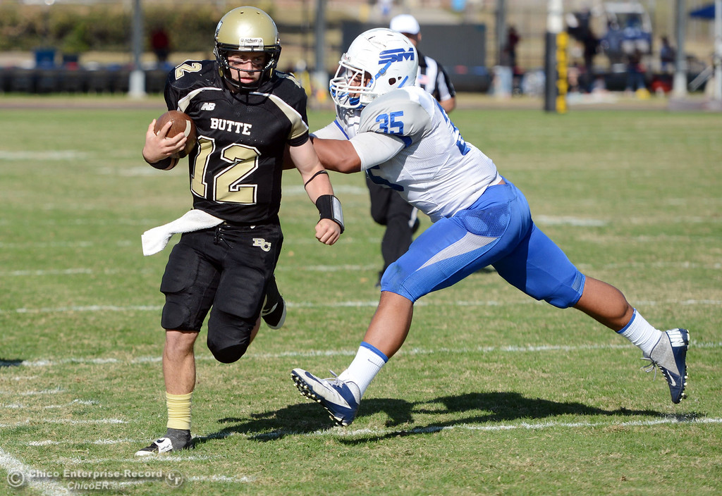 . Butte College\'s #12 Thomas Stuart (left) is pushed out of bounds against College of San Mateo\'s #35 Adam Sagapolu (right)in the second quarter of their football game at Butte\'s Cowan Stadium Saturday, November 2, 2013 in Oroville, Calif.  (Jason Halley/Chico Enterprise-Record)