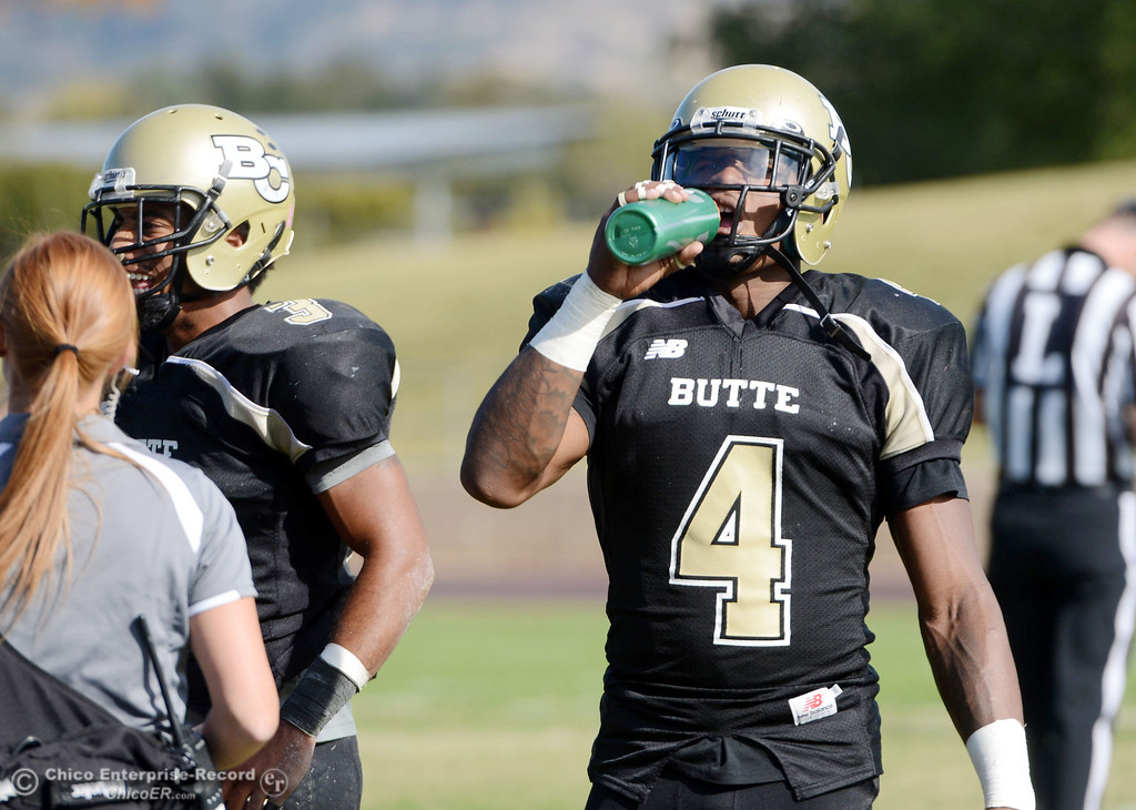 . Butte College\'s #4 Chris Edwards (right) takes a drink of water against College of San Mateo in the second quarter of their football game at Butte\'s Cowan Stadium Saturday, November 2, 2013 in Oroville, Calif.  (Jason Halley/Chico Enterprise-Record)