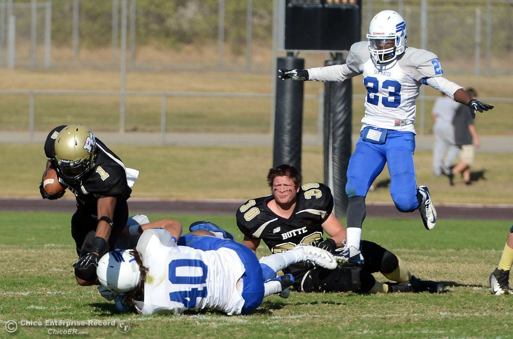. Butte College\'s #1 Wes McCoy (left) is tackled against College of San Mateo\'s #40 Jake Kearney (bottom) near #23 Bryant Hayes (right) as butte\'s #30 Eric DeLucchi (center) had his helmet knocked off in the third quarter of their football game at Butte\'s Cowan Stadium Saturday, November 2, 2013 in Oroville, Calif.  (Jason Halley/Chico Enterprise-Record)