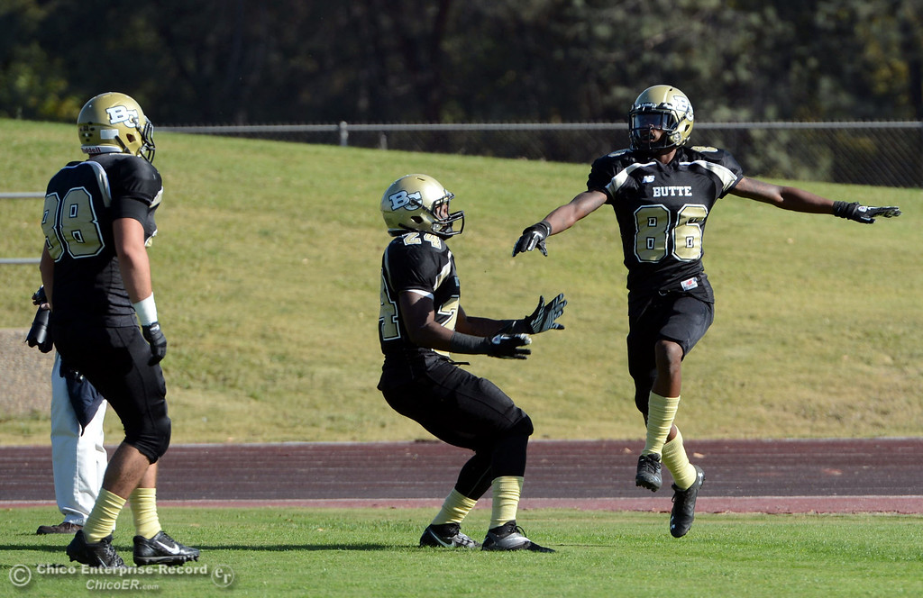 . Butte College\'s #88 Ralph Raetz (left) #24 Kendall WIlliams (center) and #86 Jon Parks (right) reacts to Parks scoring a touchdown against College of San Mateo in the second quarter of their football game at Butte\'s Cowan Stadium Saturday, November 2, 2013 in Oroville, Calif.  (Jason Halley/Chico Enterprise-Record)