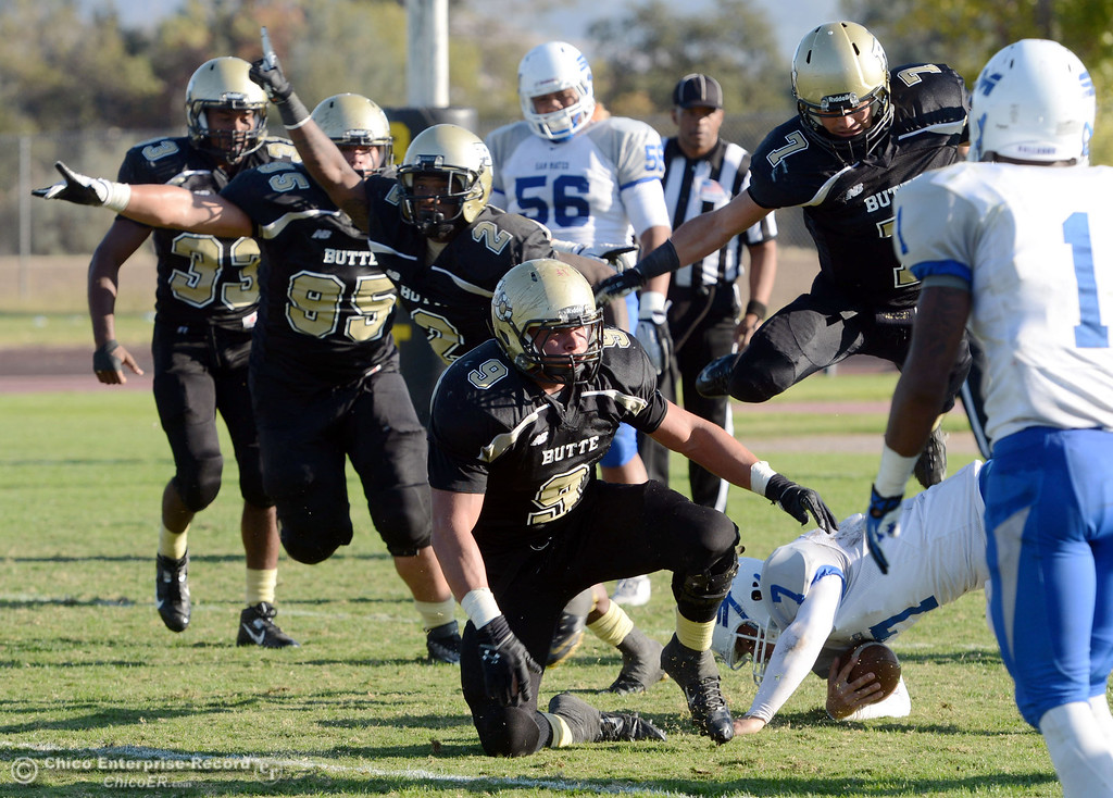. Butte College\'s #33 Jariah Booker, #95 Mark Rosenquist, #2 Deonte Flemings, #9 Tyler Adair, and #7 Ryan Holland (left to right) celebrate Adair\'s sack against College of San Mateo\'s #7 Casey Wichman (bottom) in the fourth quarter of their football game at Butte\'s Cowan Stadium Saturday, November 2, 2013 in Oroville, Calif.  (Jason Halley/Chico Enterprise-Record)