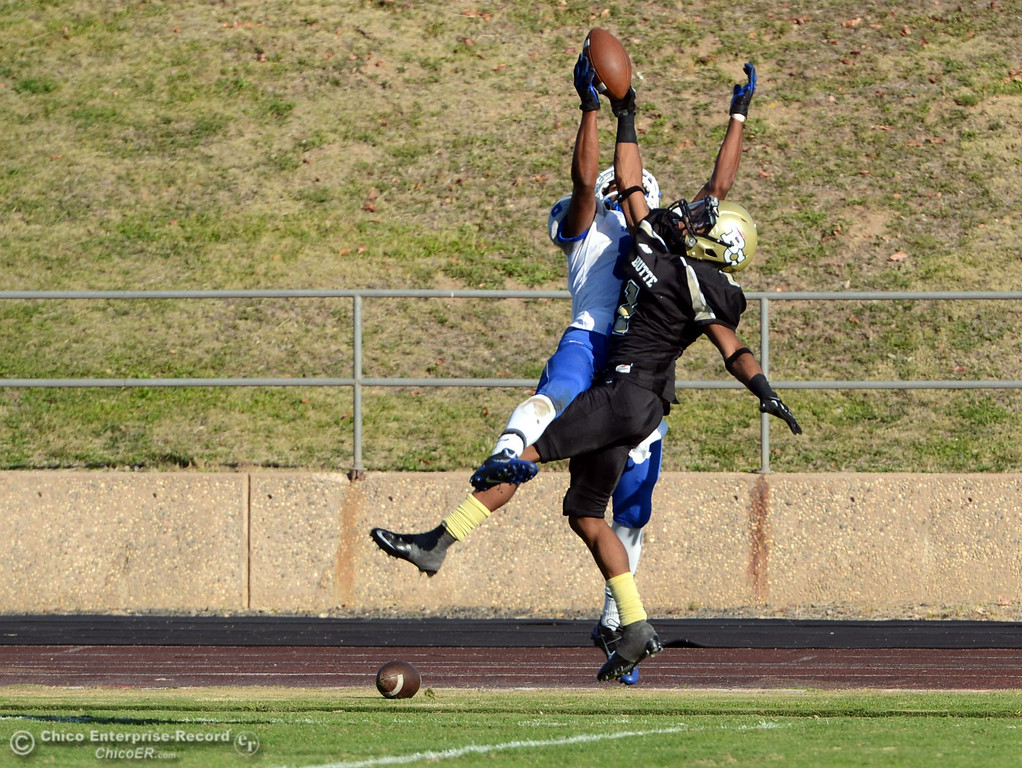 . Butte College\'s #1 Wes McCoy (right) intercepts a pass against College of San Mateo\'s #8 Raeshawn Lee (left) in the fourth quarter of their football game at Butte\'s Cowan Stadium Saturday, November 2, 2013 in Oroville, Calif.  (Jason Halley/Chico Enterprise-Record)