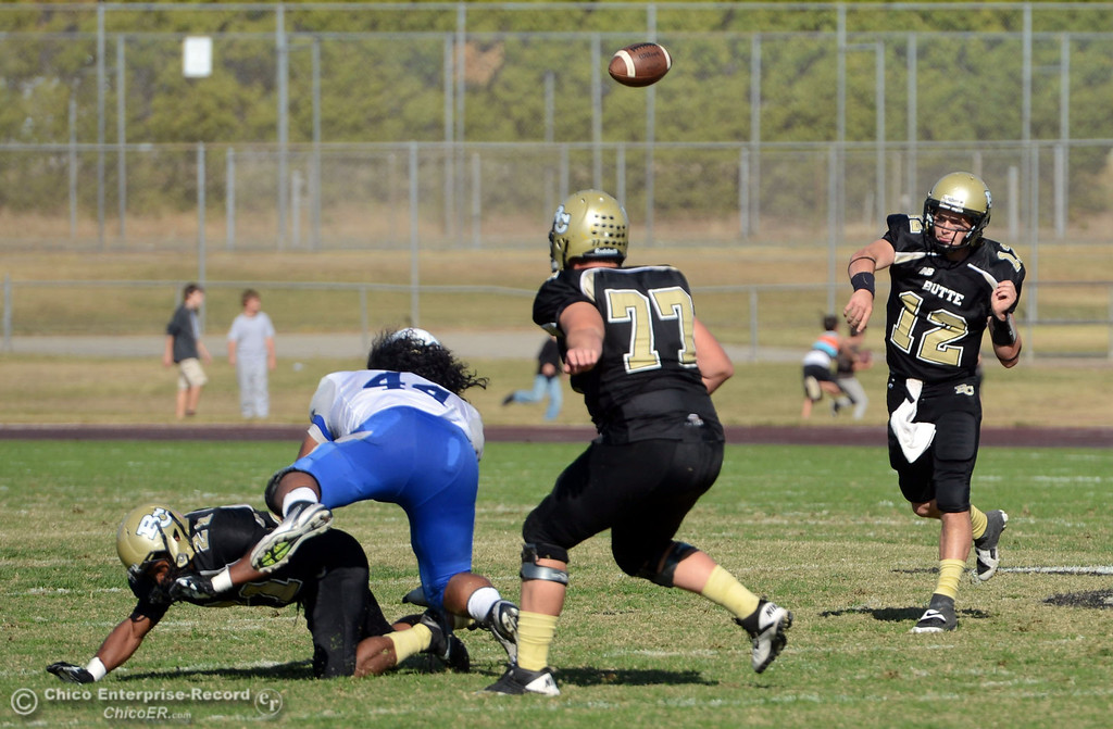 . Butte College\'s #12 Thomas Stuart (right) throws a pass to #30 Eric DeLucchi (not seen) against College of San Mateo in the second quarter of their football game at Butte\'s Cowan Stadium Saturday, November 2, 2013 in Oroville, Calif.  (Jason Halley/Chico Enterprise-Record)