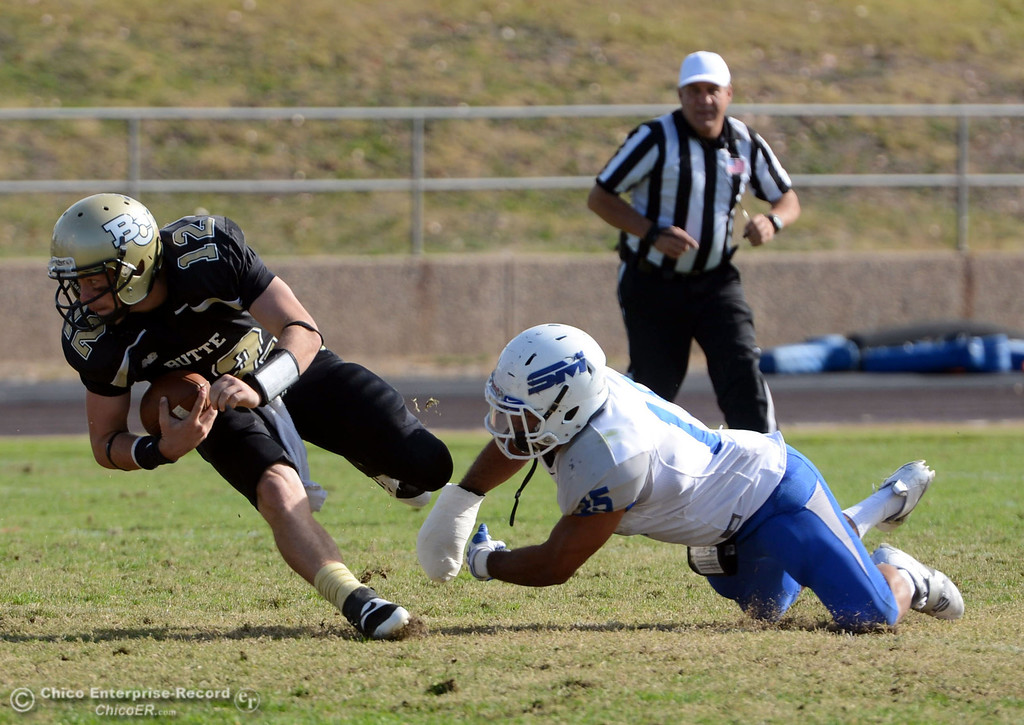. Butte College\'s #12 Thomas Stuart (left) is tripped up against San Mateo College\'s #15 Jalen Amis (right) in the first quarter of their football game at Butte\'s Cowan Stadium Saturday, November 2, 2013 in Oroville, Calif.  (Jason Halley/Chico Enterprise-Record)