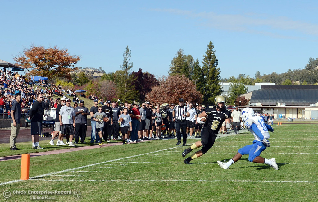 . Butte College\'s #8 Bo Brummel (left) scores a touchdown against College of San Mateo\'s #12 Taylor Mashack (right) in the second quarter of their football game at Butte\'s Cowan Stadium Saturday, November 2, 2013 in Oroville, Calif.  (Jason Halley/Chico Enterprise-Record)