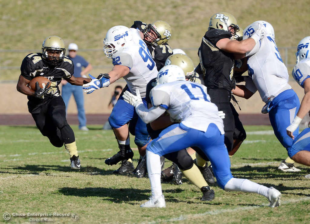. Butte College\'s #14 Robert Frazier (left) rushes against College of San Mateo\'s #92 Trevor Kelly (center) and 17 Deshane Hines (right)  in the third quarter of their football game at Butte\'s Cowan Stadium Saturday, November 2, 2013 in Oroville, Calif.  (Jason Halley/Chico Enterprise-Record)