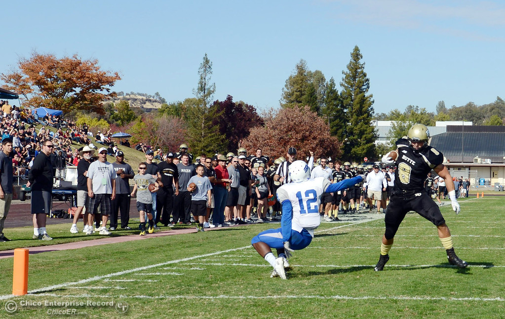. Butte College\'s #8 Bo Brummel (right) scores a touchdown against College of San Mateo\'s #12 Taylor Mashack (left) in the second quarter of their football game at Butte\'s Cowan Stadium Saturday, November 2, 2013 in Oroville, Calif.  (Jason Halley/Chico Enterprise-Record)