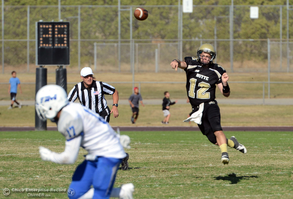 . Butte College\'s #12 Thomas Stuart (right) throws a pass against College of San Mateo in the third quarter of their football game at Butte\'s Cowan Stadium Saturday, November 2, 2013 in Oroville, Calif.  (Jason Halley/Chico Enterprise-Record)