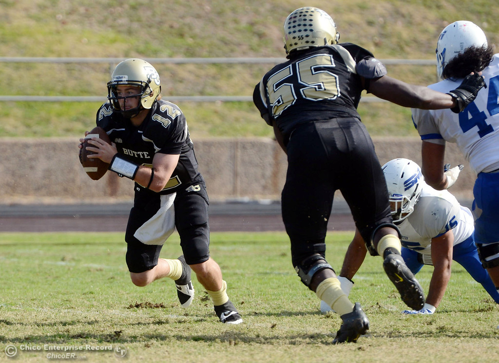 . Butte College\'s #12 Thomas Stuart scrambles against San Mateo College in the first quarter of their football game at Butte\'s Cowan Stadium Saturday, November 2, 2013 in Oroville, Calif.  (Jason Halley/Chico Enterprise-Record)