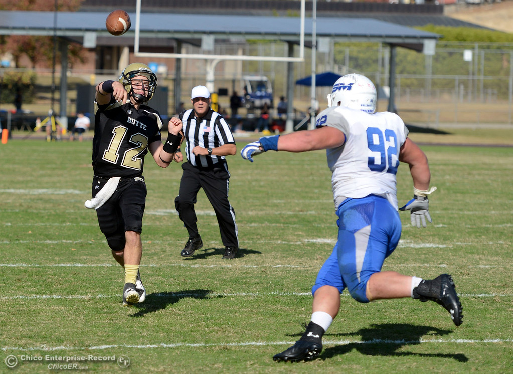 . Butte College\'s #12 Thomas Stuart (left) throws a pass against College of San Mateo\'s #92 Trevor Kelly in the second quarter of their football game at Butte\'s Cowan Stadium Saturday, November 2, 2013 in Oroville, Calif.  (Jason Halley/Chico Enterprise-Record)
