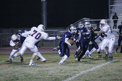 Farmersville's Anthony Azevedo (2) rushes against Strathmore's Matt Redfern (70) and Robert Pidcoe (59).