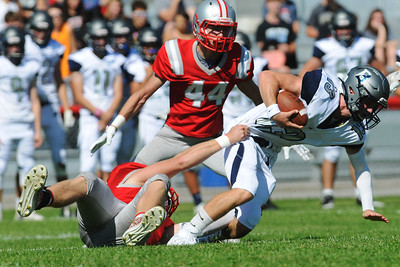 {Jack Haley/for Messenger Post Media} Canandaigua's Ryan Welch brings down Brighton quarterback Brennan Clasgens in the first half of the Braves 28-0 win over the Barons on Saturday during the final game at Evans Field.