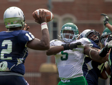 Hoyas quarterback Aaron Aiken is rushed by Wagner linebacker Jerome Williams.