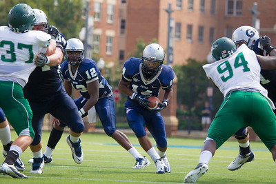 Hoyas quarterback Aaron Aiken (12) hands off to Wilburn Logan (14). Mike Lombardo  (37) and Davon Johnson (94) defend for Wagner.