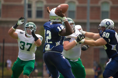 Hoyas quarterback Aaron Aiken (12) is rushed by Wagner's Mike Lombardo  (37) and Tom Lindley (76).  Kevin Sullivan (60) protects the quarterback.
