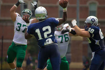 Hoyas quarterback Aaron Aiken (12) is rushed by Wagner's Mike Milone (37) and Tom Lindley (76).  Kevin Sullivan (60) protects the quarterback.
