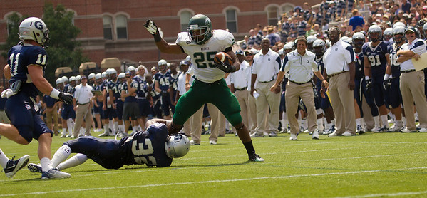 Wagner's Dominique Williams (25) tried to break a tackle by Hoyas' Jeremy Moore