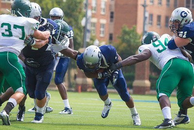 Hoyas Wilburn Logan (14) with blocking from Donald Rhodes (64) runs past Mike Lombardo (37) and Davon Johnson (94) of Wagner.