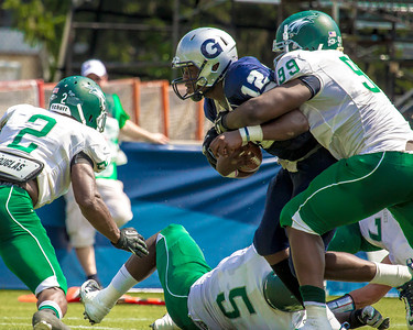 Hoyas quarterback Aaron Aiken is grabbed by Daevonte Barnett (99) of Wagner.