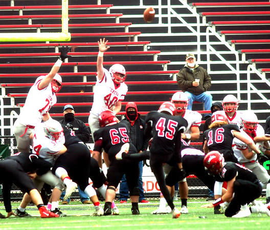 WARREN  DILLAWAY | Star Beacon <br /> Geneva's Zane Francis (40) and Matt Gruzinski (71) try to block an extra point attempt by Chardon's Nathan Tager (45) on Saturday aftrnoon during a Division III playoff game at Chardon.