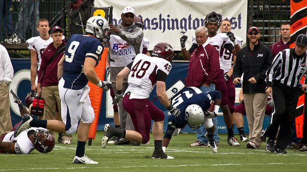 Georgetown opened the scoring in the first quarter after Isaiah Kempf  found Jamal Davis (15) open for what looked like a short pass, but Davis broke four tackles including this one from Colgate's Chris DiMassa (48) and darted down the sideline for a 63-yard touchdown. Georgetown's Tucker Stafford (9) trails on the play.