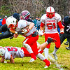 Groton-Dunstable;s Connor Estes goes airborne to lay a hit on Tyngsboro's Kyle Laforge. SUN/Ed Niser