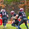 Groton-Dunstable's Michael Tammaro hands off to running back Logan Higgins as Max Morenz (front) clears the way. Sun/Ed Niser