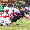 Groton-Dunstable's Mitch Townsend stretches for a first down as he is hit from left by Tyngsboro's Kyle Laforge and Kevin Butler. Sun/Ed Niser