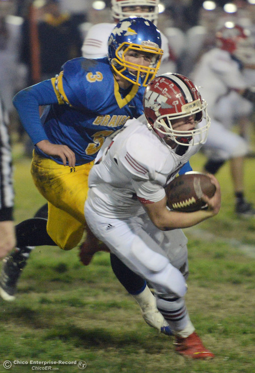 . Winters High\'s #12 Jacob Lowrie (right) runs the ball against Hamilton High\'s #3 Austin Burbank (left) in the first quarter of their football game at HHS Wednesday, November 27, 2013 in Hamilton City, Calif.  (Jason Halley/Chico Enterprise-Record)