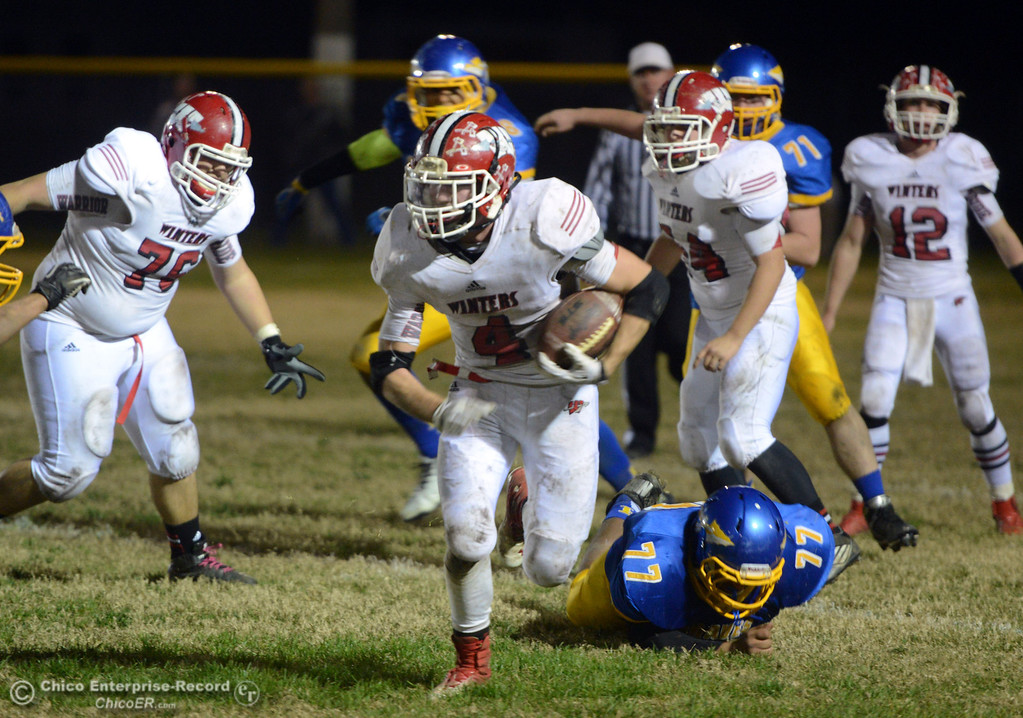 . Winters High\'s #4 Chaz Matthews (center) rushes against Hamilton High\'s in the third quarter of their football game at HHS Wednesday, November 27, 2013 in Hamilton City, Calif.  (Jason Halley/Chico Enterprise-Record)