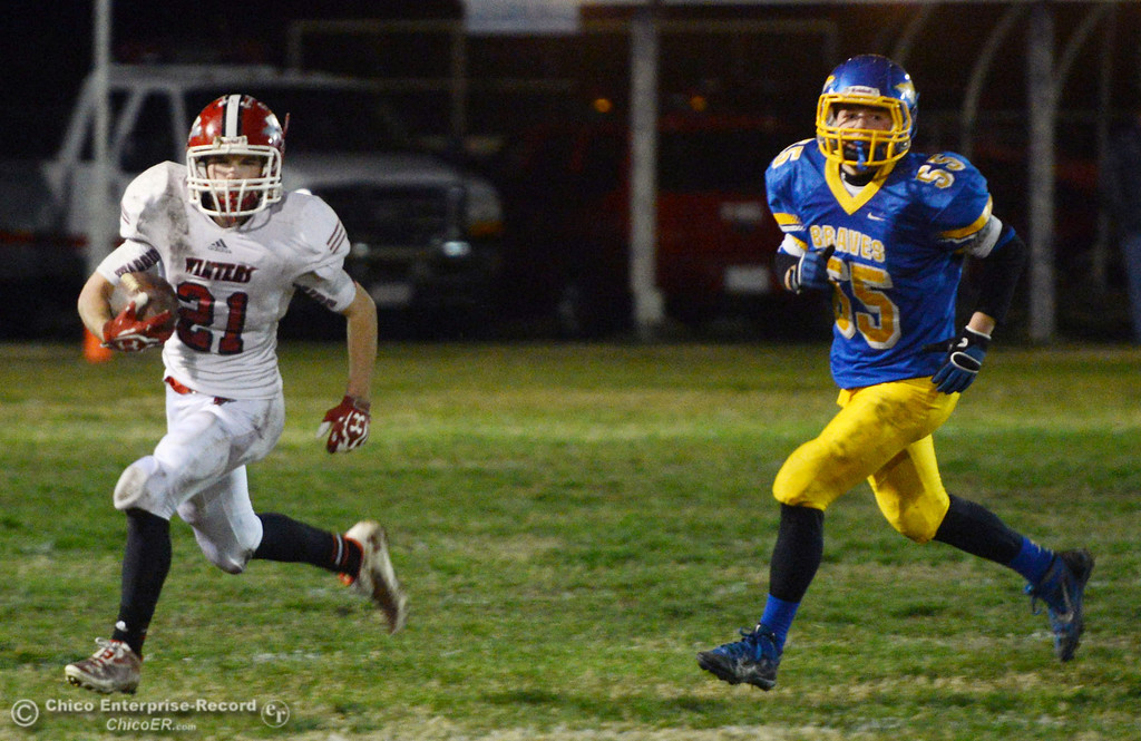 . Winters High\'s #21 Trevor Ray (left) rushes against Hamilton High\'s #55 Chad Young (right) in the fourth quarter of their football game at HHS Wednesday, November 27, 2013 in Hamilton City, Calif.  (Jason Halley/Chico Enterprise-Record)