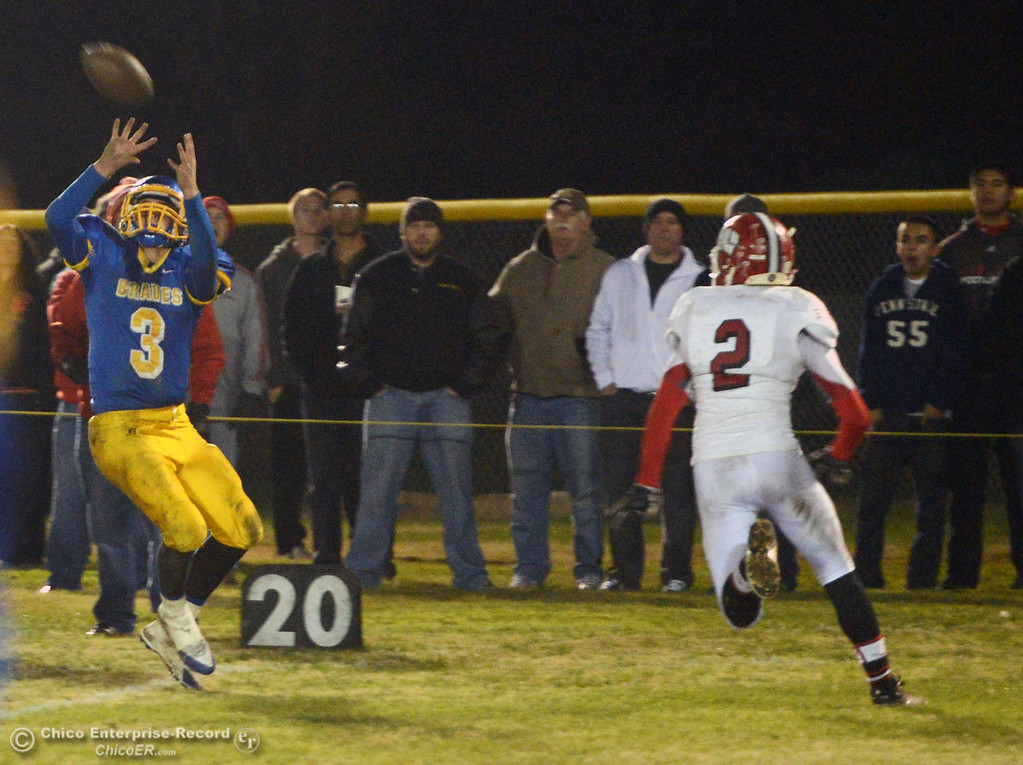 . Hamilton High\'s #3 Austin Burbank (left) completes a catch against Winters High\'s #2 Christian Corrales (right) in the second quarter of their football game at HHS Wednesday, November 27, 2013 in Hamilton City, Calif.  (Jason Halley/Chico Enterprise-Record)