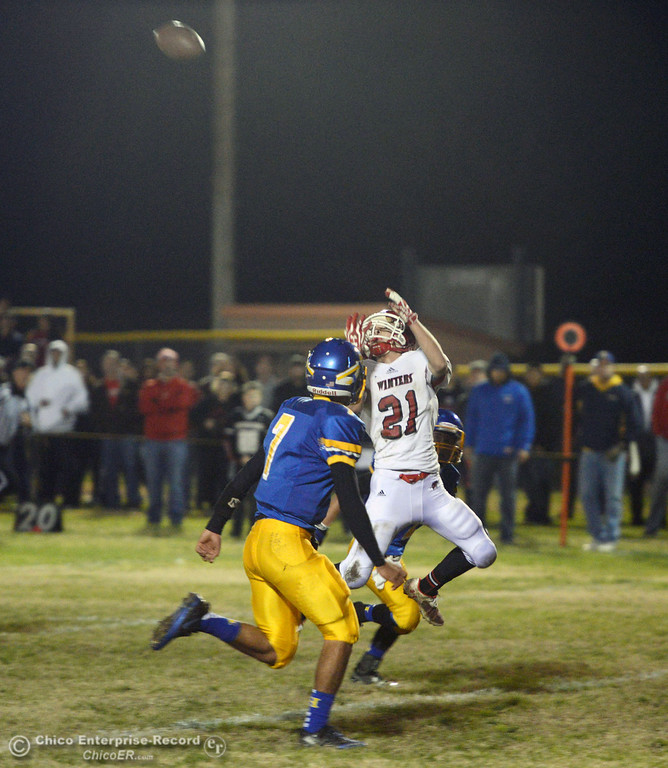 . Hamilton High\'s #7 Ricky Pompa (left) watches Winters High\'s #21 Trevor Ray (right) complete a catch in the first quarter of their football game at HHS Wednesday, November 27, 2013 in Hamilton City, Calif.  (Jason Halley/Chico Enterprise-Record)