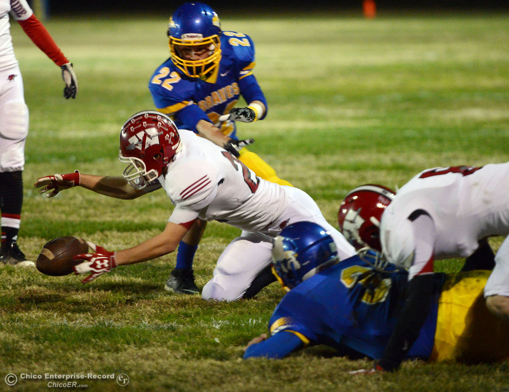 . Hamilton High against Winters High\'s #21 Trevor Ray (center) picks up a fumble against Hamilton High\'s #3 Austin Burbank (right) as #Luis Ojeda (top) in the first quarter of their football game at HHS Wednesday, November 27, 2013 in Hamilton City, Calif.  (Jason Halley/Chico Enterprise-Record)