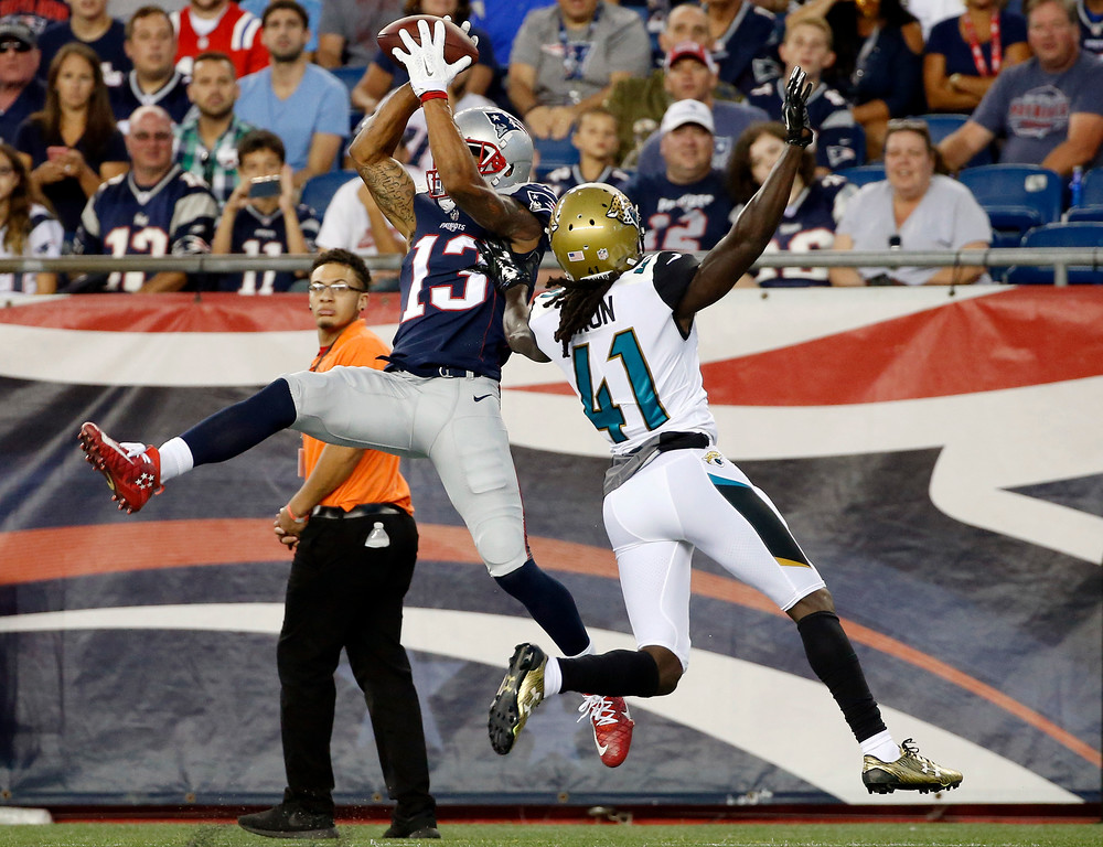 . New England Patriots wide receiver Devin Lucien (13) tries to catch a pass in front of Jacksonville Jaguars cornerback Brian Dixon (41) in the first half of an NFL preseason football game, Thursday, Aug. 10, 2017, in Foxborough, Mass. Lucien landed out of bounds. (AP Photo/Mary Schwalm)