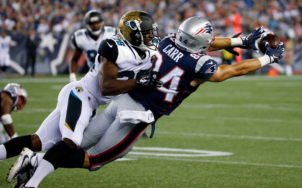 . New England Patriots wide receiver Austin Carr (84) stretches for a catch in front of Jacksonville Jaguars cornerback Doran Grant (26) in the second half of an NFL preseason football game, Thursday, Aug. 10, 2017, in Foxborough, Mass. (AP Photo/Mary Schwalm)