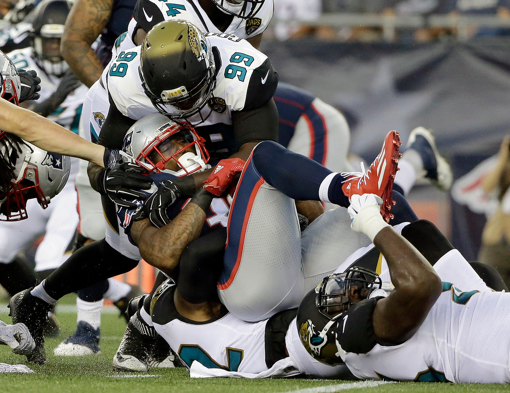 . Jacksonville Jaguars defensive end Malliciah Goodman (99) tackles New England Patriots running back Brandon Bolden in the first half of an NFL preseason football game, Thursday, Aug. 10, 2017, in Foxborough, Mass. (AP Photo/Steven Senne)