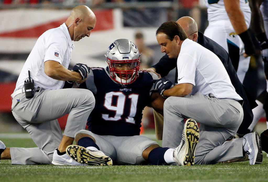 . New England Patriots defensive end Deatrich Wise, center, receives attention on the field after an injury in the first half of an NFL preseason football game against the Jacksonville Jaguars, Thursday, Aug. 10, 2017, in Foxborough, Mass. (AP Photo/Mary Schwalm)