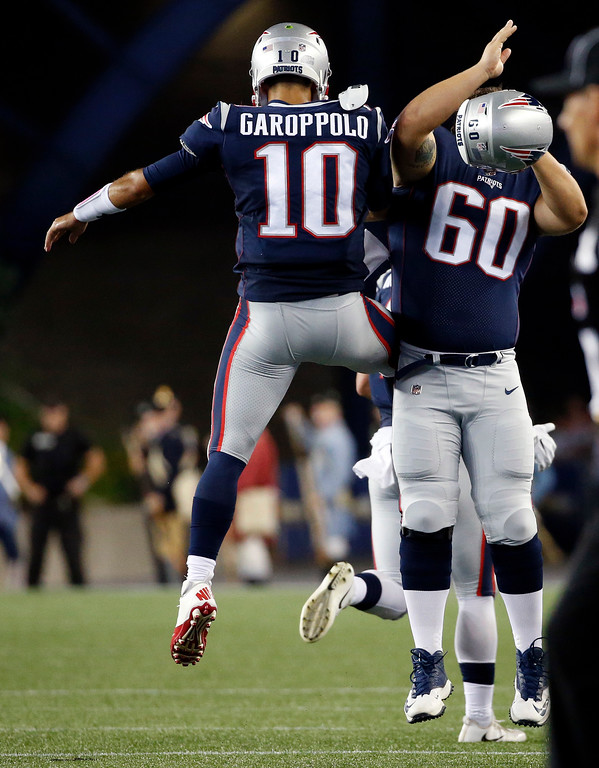 . New England Patriots quarterback Jimmy Garoppolo, right, celebrates his touchdown pass to Austin Carr with center David Andrews (60) in the first half of an NFL preseason football game against the Jacksonville Jaguars, Thursday, Aug. 10, 2017, in Foxborough, Mass. (AP Photo/Mary Schwalm)