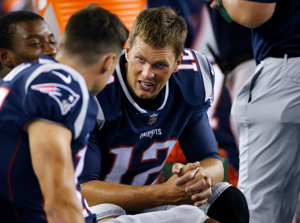 . New England Patriots quarterback Tom Brady (12) talks to teammates on the sideline in the second half of an NFL preseason football game against the Jacksonville Jaguars, Thursday, Aug. 10, 2017, in Foxborough, Mass. (AP Photo/Mary Schwalm)