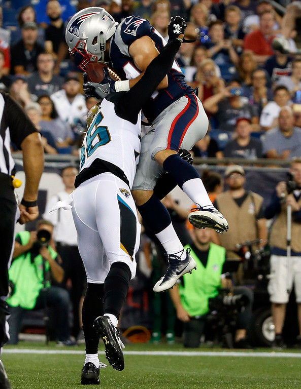 . New England Patriots wide receiver Austin Carr, top, catches a touchdown pass in the grasp of Jacksonville Jaguars cornerback Tracy Howard in the first half of an NFL preseason football game, Thursday, Aug. 10, 2017, in Foxborough, Mass. (AP Photo/Mary Schwalm)