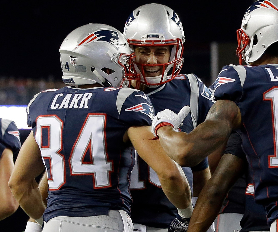 . New England Patriots quarterback Jimmy Garoppolo, center, celebrates his touchdown pass to Austin Carr, left, in the first half of an NFL preseason football game against the Jacksonville Jaguars, Thursday, Aug. 10, 2017, in Foxborough, Mass. (AP Photo/Steven Senne)