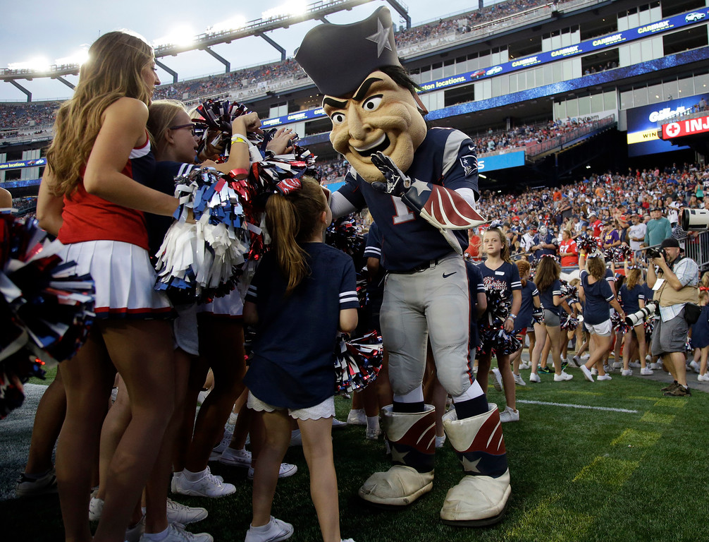 . New England Patriots mascot Pat Patriot greets dancers during the first half of an NFL preseason football game between the Patriots and the Jacksonville Jaguars, Thursday, Aug. 10, 2017, in Foxborough, Mass. (AP Photo/Mary Schwalm)