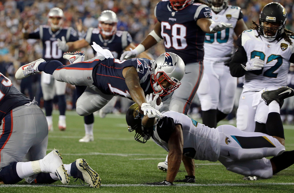 . New England Patriots wide receiver K.J. Maye dives over Jacksonville Jaguars linebacker Josh McNary for a touchdown in the second half of an NFL preseason football game, Thursday, Aug. 10, 2017, in Foxborough, Mass. (AP Photo/Steven Senne)