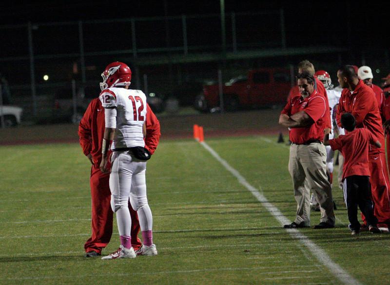 Lindsay quarterback Alex Jara discusses the next play with Cardinal head coach Jesse Lira.
