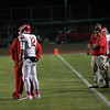 Lindsay quarterback Alex Jara discusses the next play with Cardinal head coach Jesse Lira.