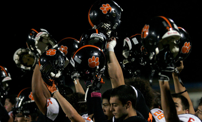 Woodlake Tigers raise their helmets during the playing of the National Anthem before their game against the Lindsay Cardnials.