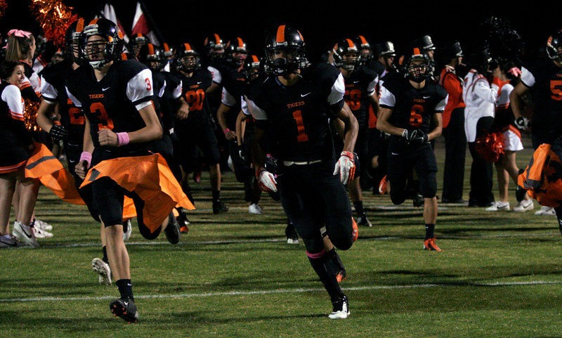 Woodlake Tiger Elijah Cunningham (1) leads his team onto the field before the Tiger's game against Lindsay on October 25, 2013.