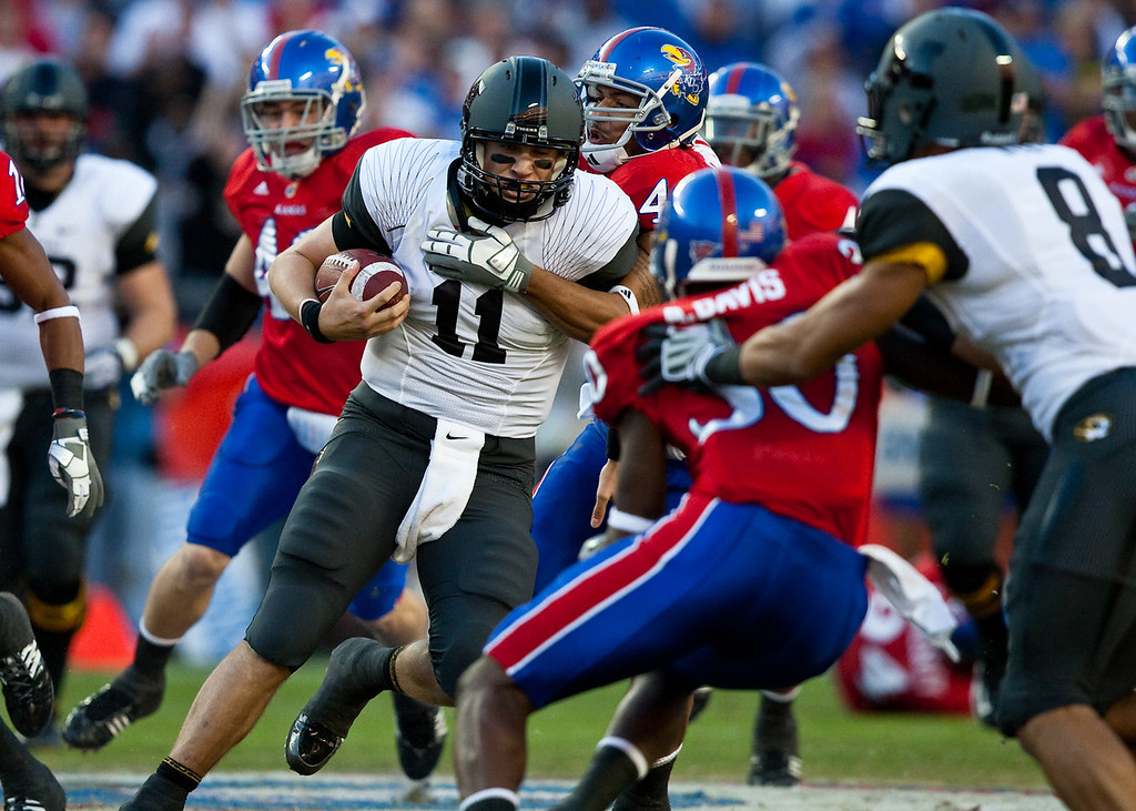 28 November 2009: Missouri quarterback Blaine Gabbert (11) keeps the ball and is tackled by Kansas cornerback Justin Thornton (46) during the Missouri Tigers 41-39 win over the Kansas Jayhawks at Arrowhead Stadium in Kansas City, Missouri.