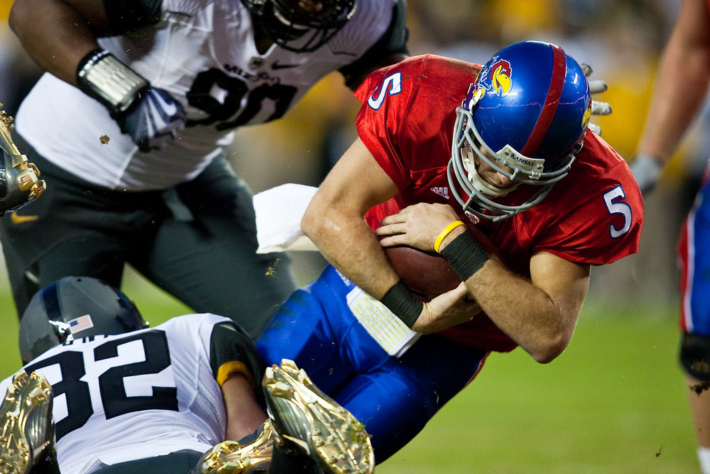 28 November 2009: Kansas quarterback Todd Reesing (5) is tackled by Missouri linebacker Will Ebner (32) during the Missouri Tigers 41-39 win over the Kansas Jayhawks at Arrowhead Stadium in Kansas City, Missouri.